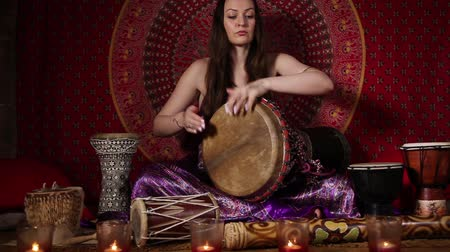 vurmalı : Young adult woman playing drum during meditation session