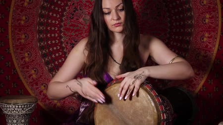 vurmalı : Young woman relaxing with a drum indoors. Audio included