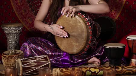 vurmalı : Tilt up video shot of a woman playing  drum indoors. Audio included