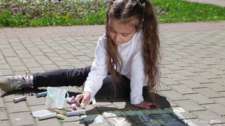 preschool : Little girl draws with chalk on the pavement in the street  at sunny day Stock Footage