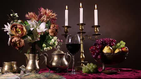 tarz : Still life with dried flowers, candles and fruit vase on dark background in Dutch style Stok Video