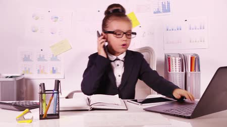 inteligentní : Worried business girl talking on the phone sitting in a desktop at office