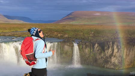 mocný : Girl tourist enjoys the view of the Godafoss waterfall with a rainbow in Iceland