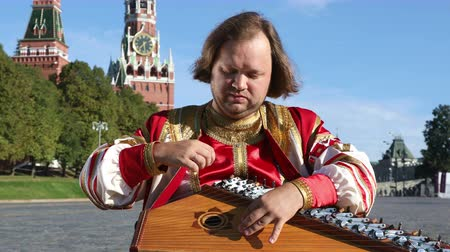 gusli : The musician in traditional Russian clothes plays an old Russian musical instrument gusli on the background of the Kremlin on red Square. Moscow, Russia