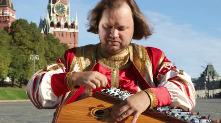folklór : Performer in traditional Russian clothes plays an old Russian musical instrument gusli on the background of the Kremlin on red Square. Moscow, Russia
