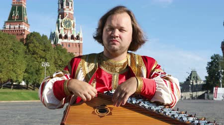gusli : The minstrel in traditional Russian clothes plays an old Russian musical instrument gusli on the background of the Kremlin on red Square. Moscow, Russia