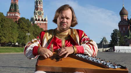 gusli : The musician in traditional Russian clothes plays an old Russian musical instrument gusli on the background of the Kremlin and St. Basils Cathedral on red Square. Moscow, Russia