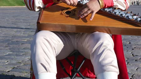 gusli : Folk musician in traditional Russian clothes plays an old Russian musical instrument gusli on the background of the Kremlin on red Square. Moscow, Russia