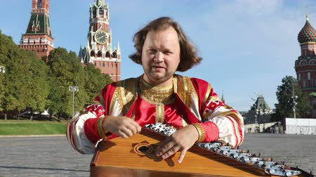 gusli : The musician in traditional Russian clothes plays an old Russian musical instrument gusli on the background of the Kremlin on red Square in Moscow, Russia