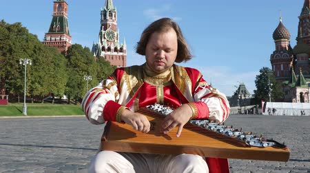folklór : Folk performer in traditional Russian clothes plays an old Russian musical instrument gusli on the background of the Kremlin and St. Basils Cathedral on red Square. Moscow, Russia