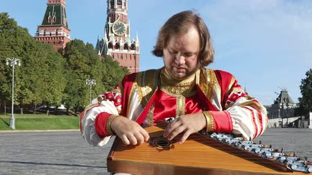 gusli : Folk minstrel in traditional Russian clothes plays an old Russian musical instrument gusli on the background of the Kremlin and St. Basils Cathedral on red Square. Moscow, Russia