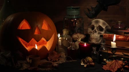 dekoracje : Scary still life with skull, pumpkin, old books, maple leaves, vintage bottles and candles on witch table. Halloween or esoteric concept.