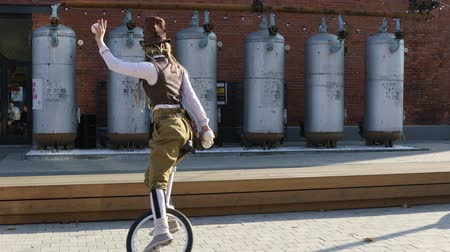 žolík : Young girl clown rides a unicycle and juggles balls outdoors