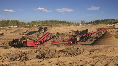 důl : Heavy machinery - excavators and trucks working in the quarry. Quarry sand with a grinding machine and conveyor belt