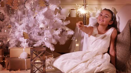 decorating : Little pretty girl is burning a sparkler sitting under a Christmas tree in the evening at home