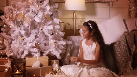tempo de natal : Little pretty girl decorating Christmas tree with toys in the evening at home