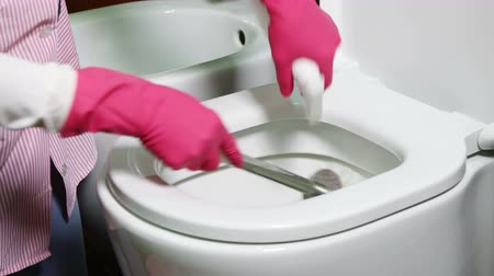 banheiro : Woman wearing pink gloves cleaning toilet bowl in bathroom at home or hotel room using liquid cleaner and brush
