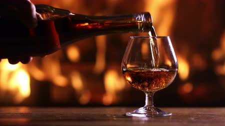 goblet : A mans hand pours brandy from a bottle into a glass on the background of a burning fireplace Stock Footage