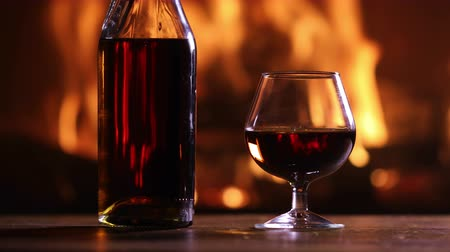 şarap kadehi : A bottle of brandy and a glass are on the table against the burning fireplace Stok Video