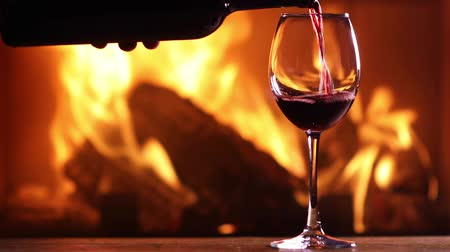 şömine : A mans hand pours red wine from a bottle into a glass on the background of a burning fireplace Stok Video