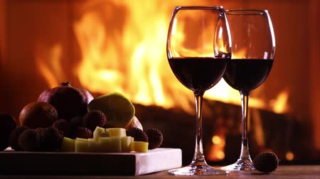 şarap kadehi : Two glasses of wine and a plate of fruit and cheese on the background of a burning fireplace