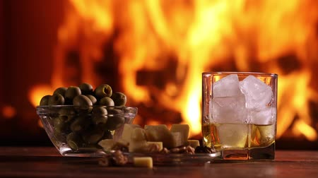 A mans hand pours whisky from a bottle into a glass on the background of a burning fireplace