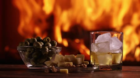 A glass of whisky and plate with cheese, olives and nuts are on the table on the background of a burning fireplace