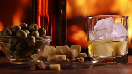 A bottle of whisky and a glass with some snacks are on the table against the burning fireplace Стоковые видеозаписи