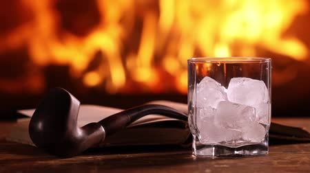 A mans hand pours whisky from a bottle into a glass on the background of a burning fireplace. Next to a glass of whiskey on the table are an open book and a smoking pipe Стоковые видеозаписи