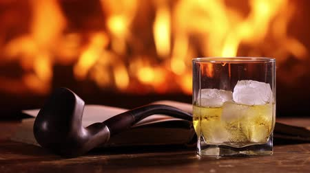 A glass of whisky, an open book, and a smoking pipe on the table on the background of a burning fireplace