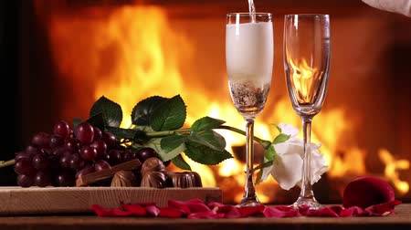 Pouring sparkling wine into glasses on the background of a burning fireplace. Next to a glasses of sparkling wine on the table are plate with grapes, chocolate and white rose Стоковые видеозаписи