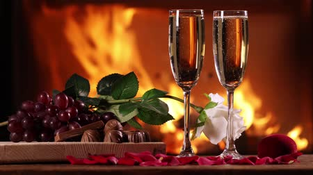 Still life of a two glasses of sparkling wine and a fruit plate, chocolate and rose on the background of a burning fireplace Стоковые видеозаписи