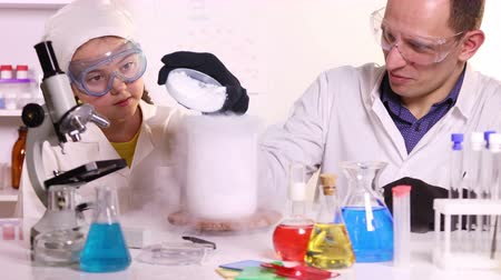 A young scientist conducts chemistry classes for a schoolgirl doing experiments with liquid nitrogen and dry ice in a chemical laboratory