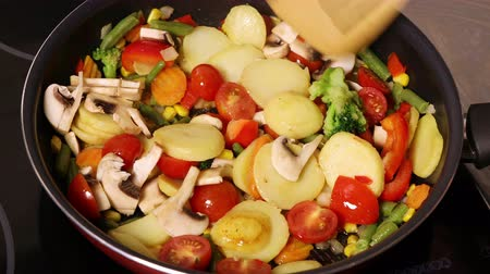 Mushrooms with vegetables are fried in a pan and stirred with a wooden spatula