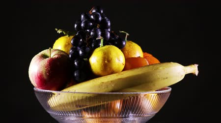 A vase with fresh fruit and water droplets on them rotating on a black background
