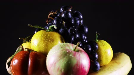 Fresh fruit and water droplets on them rotating on a black background