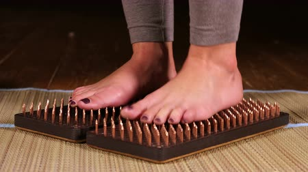 Womens feet standing on a bed of nails