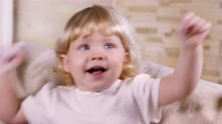 Little blond girl laughing in front of the camera indoors Стоковые видеозаписи