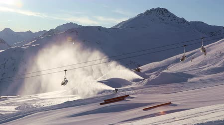Ski chairlift and working snow cannons in the bright sun on the background of the snow covered Dolomites. Livigno, Italy