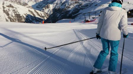 Young adult sportswoman in a ski suit and helmet skiing on an empty ski slope in the Dolomites, Livigno Italy Стоковые видеозаписи