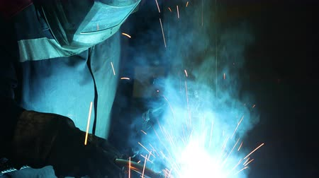 Working welder at the factory in a protective suit welds metal details in shop. Industrial theme Стоковые видеозаписи