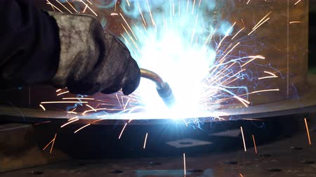 Bright sparks from welding equipment while the welder is working in an industrial shop