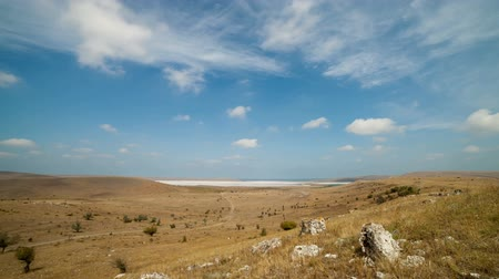 широкий : Clouds float over the fields and dry lake. Timelapse.