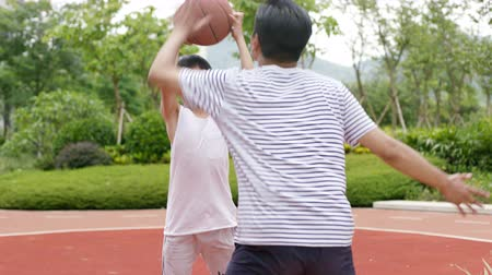 sahte : Asian kid doing shot fake when playing basketball with father outdoor in playground in slow motion Stok Video