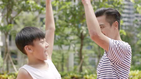 sararmış : Asian father & son making a high five after outdoor sport game in slow motion