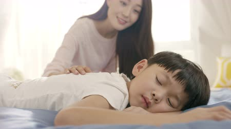 matrace : close up of young Asian mother smiling & waking up her son in morning Dostupné videozáznamy