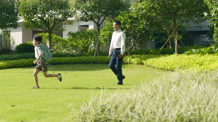 go to school : Asian boy going through garden to school with his father