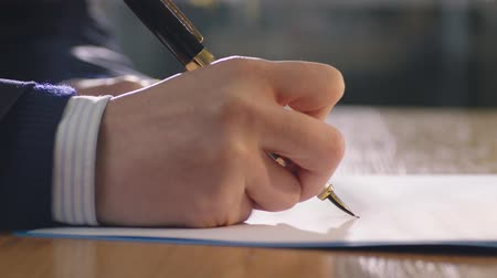 hong kong : closeup of hand holding pen and signing on document
