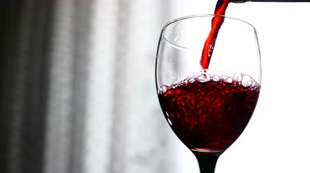 şarap kadehi : red wine pouring into a glass on light background Stok Video