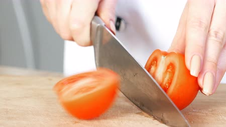 tábua de cortar : woman cook cuts fresh tomato, hands closeup